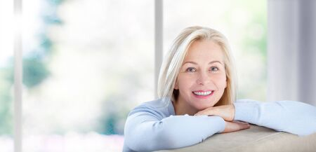 Beautiful business woman smiling friendly and looking in camera near the window in office. Stock Photo