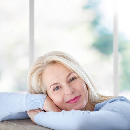 Beautiful business woman smiling friendly and looking in camera near the window in office.