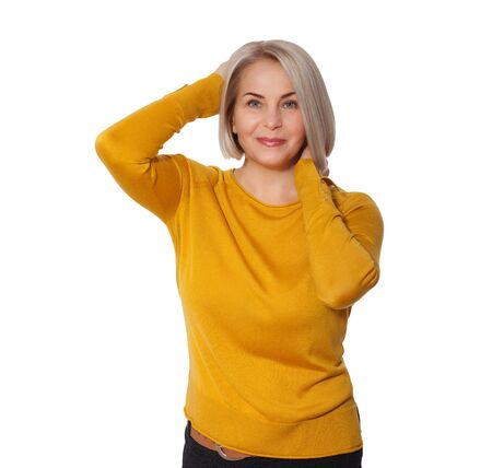 Middle aged blonde emotionally posing in a studio. Happy woman in yellow bright sweater on white background Stock Photo