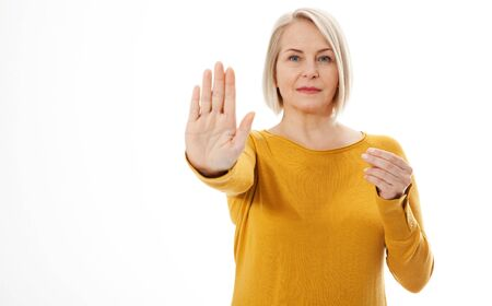 Attractive middle aged woman in a bright yellow sweater holds an empty hand for an anti-advertisement product. Excited woman showing the sign of stop Stock fotó