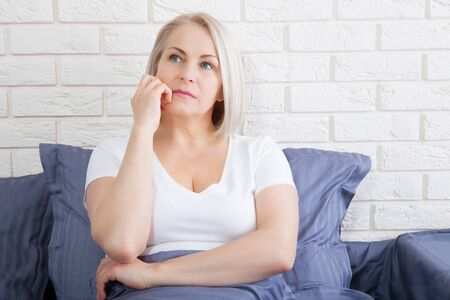 Sad woman sitting on the bed at the morning. Depressed menopause.