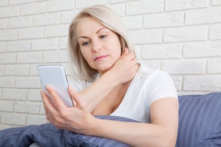 Sad senior woman sitting on bed using smart phone.