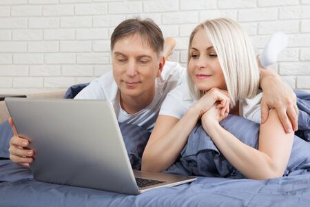 Smiling attractive couple lying on bed using laptop communicating online at home, happy man and woman typing on computer, enjoying internet shopping or chatting in social networks in bedroom.