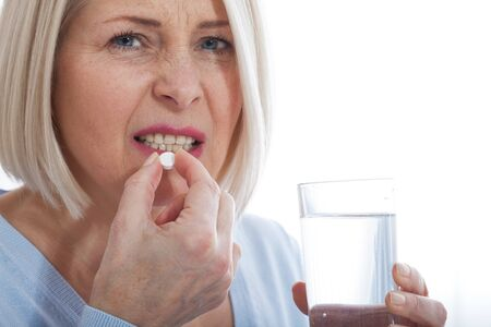 medicine, health care and people concept, close up of middle aged woman taking in pill