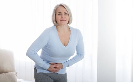 Middle aged woman suffering from abdominal pain while at home