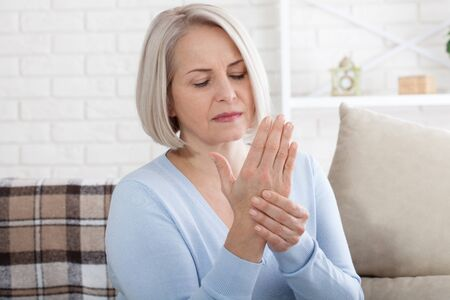 Middle aged woman suffering from pain in hands, closeup. Woman massaging her arthritic hand and wrist