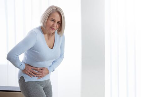 Woman in pain holding her stomach on the right side. Concept photo with indicating location of the pain. Health care concept