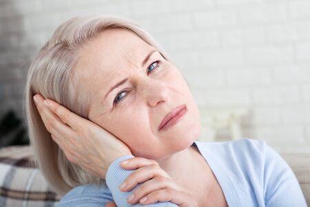 Tinnitus. Nahaufnahme des Seitenprofils kranke Frau mit Ohrenschmerzen, die ihren schmerzhaften Kopf berühren. Konzeptfoto mit Angabe der Schmerzstelle. Gesundheitskonzept