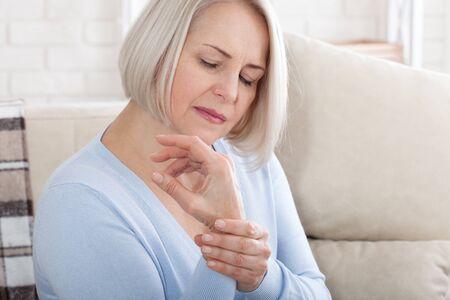 Woman massaging her arthritic hand and wrist
