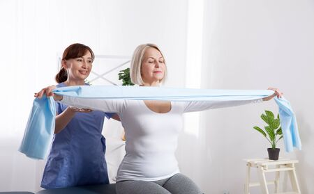 Physiotherapist and woman sitting on a bed exercising with a rubber tape Foto de archivo