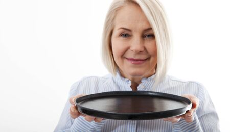 Kitchen woman gives empty black plate for your advertising products isolated on white background. Mock up for use
