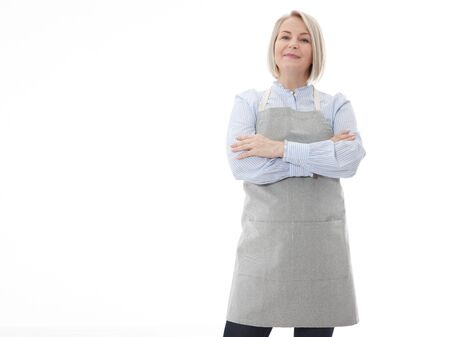 Woman in apron. Confident beautyful woman in apron keeping arms crossed and smiling while standing against white background