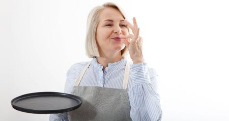 Chef woman showing sign for delicious. Female chef in uniform with perfect sign holding empty plate. Satisfied chef, cook or baker gesturing excellent. Cook with taste approval gesture. Mock up.