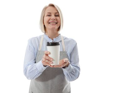 Part-time job coffee break relax leisure pause concept. Friendly pleasant woman barista giving big latte isolated on gray background copy-space
