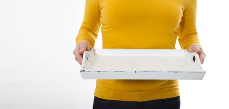 Kitchen woman gives empty tray for your advertising products isolated on white background. Mock up for use