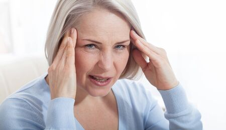 Woman suffering from stress or a headache grimacing in pain