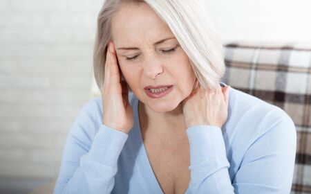 Woman suffering from stress or a headache grimacing in pain as she holds the back of her neck with her other hand to her temple