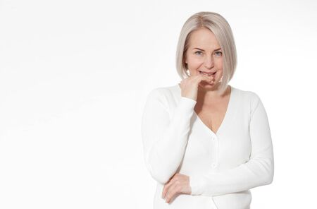 Attractive Middle Aged Woman Smiles emotionally posing in studio on white Foto de archivo