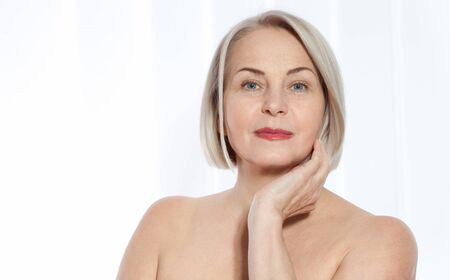 Beautiful middle-aged blonde woman shows off her perfectly well-groomed face. Plastic surgery collagen injections. Macro face. Selective focus on face. Realistic images with their own imperfections.