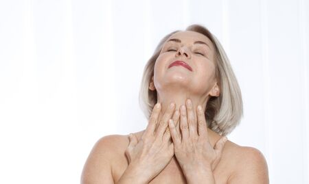 Portrait of cheerful senior woman smiling while looking away at spa. Happy mature woman after spa massage and anti-aging treatment on face. Realistic images with their own imperfections.