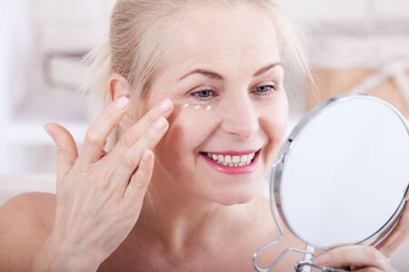 Middle aged woman looking at wrinkles in mirror. Plastic surgery and collagen injections. Makeup. Macro face. Selective focus Foto de archivo