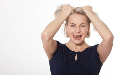 Happy woman emotionally posing in studio. Middle aged woman on white background