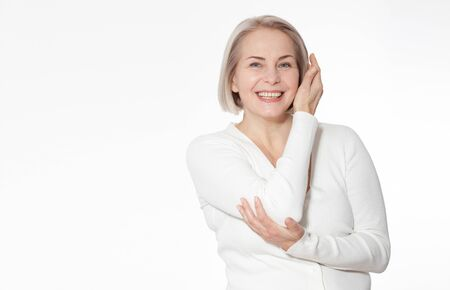 Happy woman emotionally posing in a studio. Happy woman in yellow bright sweater on white background