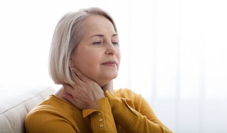 Sore throat middle aged woman at home.