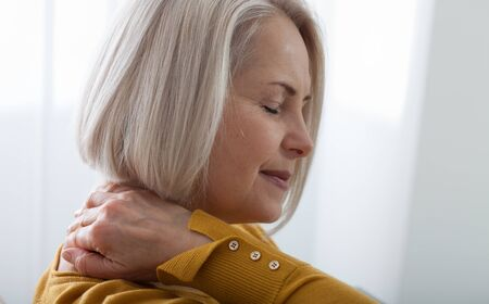 Woman with pain in her neck, medical shot at home. Concept photo with indicating location of the pain.