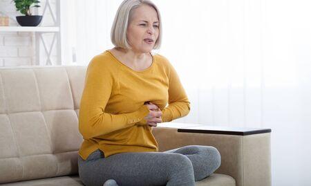 Portrait of middle aged woman having heart attack Foto de archivo