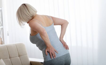 Middle aged woman with pain in the backache and lower back. Concept photo with indicating location of the pain. Health care concept