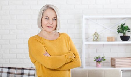 Active beautiful middle aged woman smiling friendly and looking in camera in living room. Womans face closeup. Realistic images without retouching with their own imperfections. Selective focus.