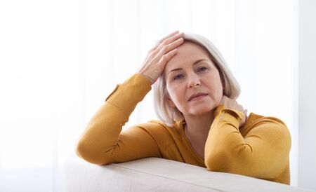 Woman suffering from stress or a headache grimacing in pain as she holds the back of her neck with her other hand to her temple, with copyspace. Concept photo with indicating location of pain.