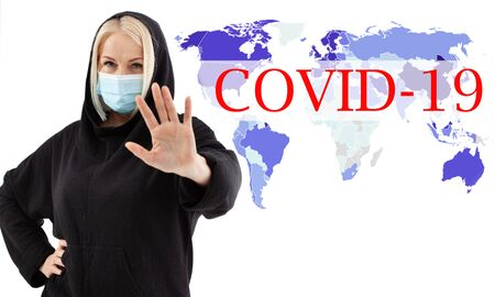 Woman wearing face mask. Concept coronavirus, respiratory virus. Sign with hands stop. Text Covid-19 Foto de archivo