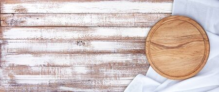 Empty pizza board and tablecloth on wooden deck table with napkin Foto de archivo