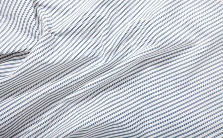 White and blue striped fabric texture with creased folds Foto de archivo