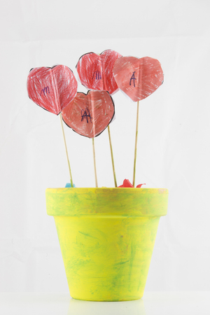 yellow pot with flowers of hearts