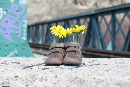 Baby shoes with yellow flowers on an iron bridge