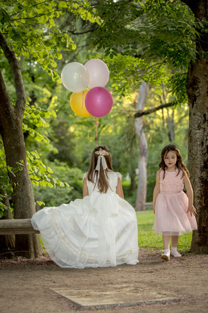Girls of communion in a park in Madrid, Spain Banco de Imagens - 124821712