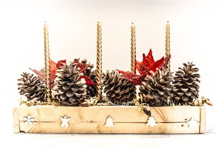 Christmas center with pine cones, acorns, candles and red flowers