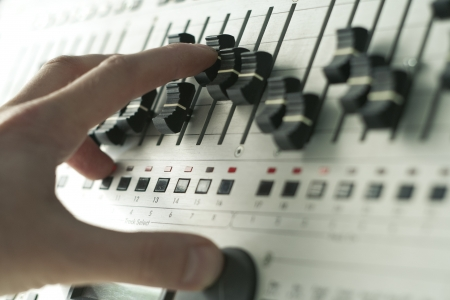 hand of dj tweaking knobs and moving sliders on club mixer photo
