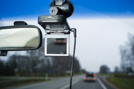 rear view mirror with portable car camcorder, gprs navigator on windscreen, shot from passenger front seat
