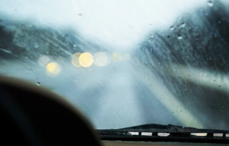 blurred view of a slippy road, headlights ahead, concept of driving in bad weather Фото со стока