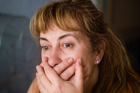 image of a shocked l woman covering her mouth with her hands photo