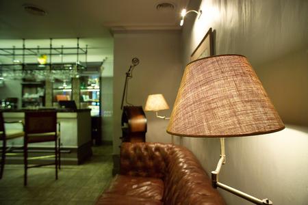 brown leather sofa: lampada e divano in pelle marrone Archivio Fotografico