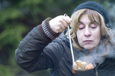 portrait of a woman tasting a hot soup, outdoor shot photo