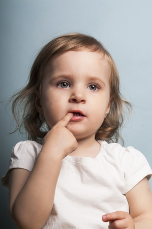 nice portrait of a baby girl with a distant gaze, biting her finger, studio shot on blue photo