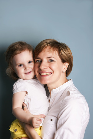 Portrait of a young woman holding her beautiful baby,vertical  studio shot on blue photo