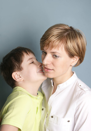 Image of a little boy telling a secret to his mother, vertical studio shot photo
