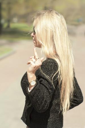 finer: mujer rubia flipping el p�jaro, tiro vertical al aire libre